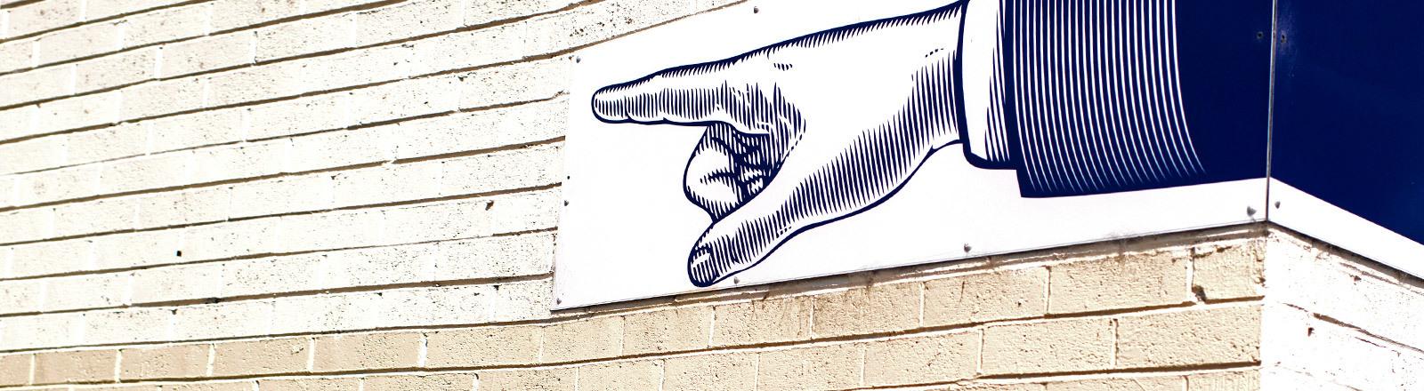 Ein Bild an einer Wand, das einen ausgestreckten Finger zeigt.
