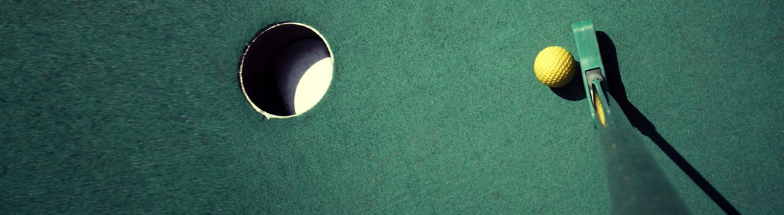 Ein Loch, ein Ball und ein Schläger beim Minigolf