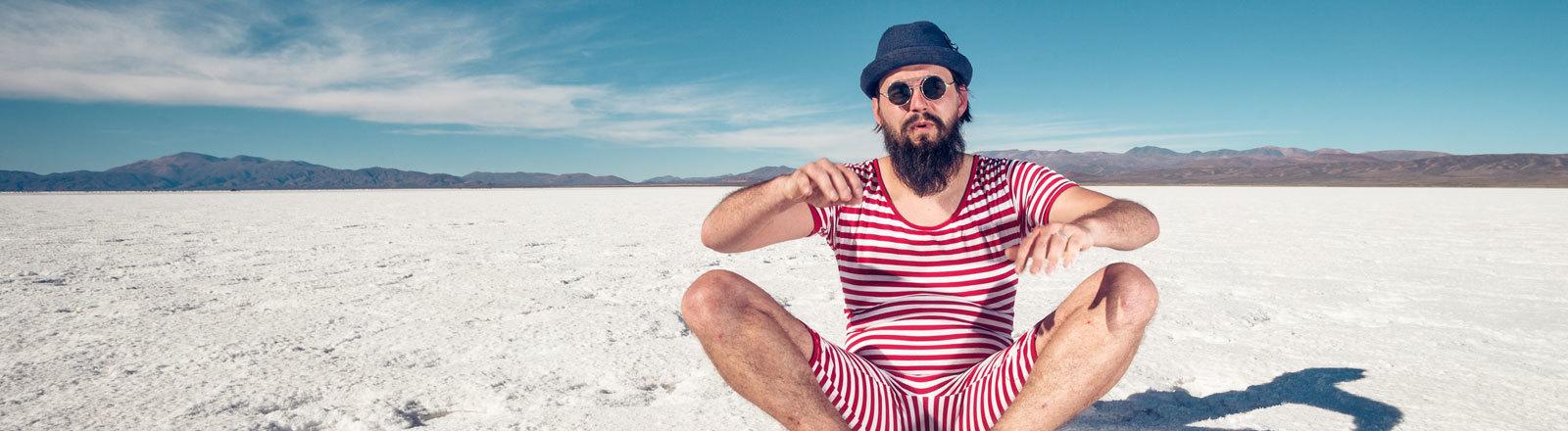Ein Mann sitzt auf Sand