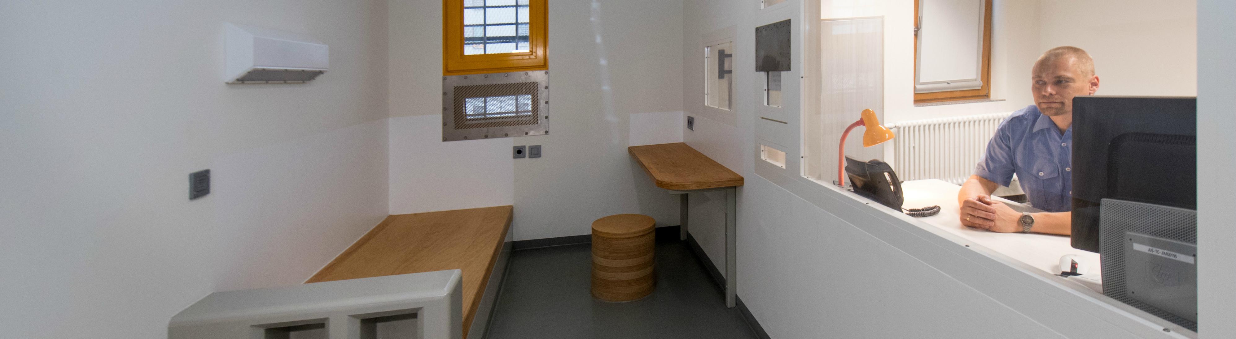 Ein Justizbeamter sitzt hinter der Scheibe und blickt in den gitterlosen Haftraum in der JVA Dresden.