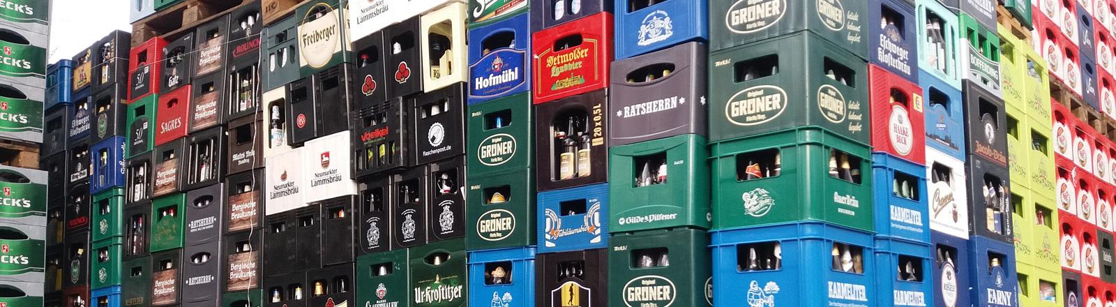 Leere Bierkästen unterschiedlicher Brauereien stehen auf Paletten gestapelt