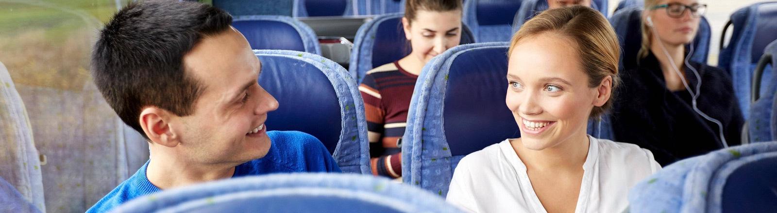Ein Mann und eine Frau lächeln sich an, während sie im Bus fahren.