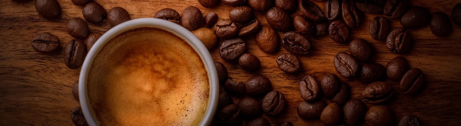 Eine Tasse Espresso von oben fotografiert. Auf dem Holztisch liegen noch Kaffeebohnen.