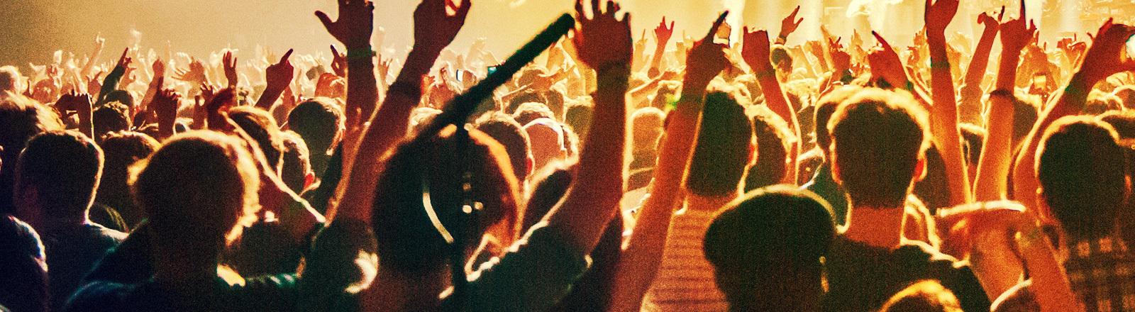 Menschen feiern in einem Club und tanzen.
