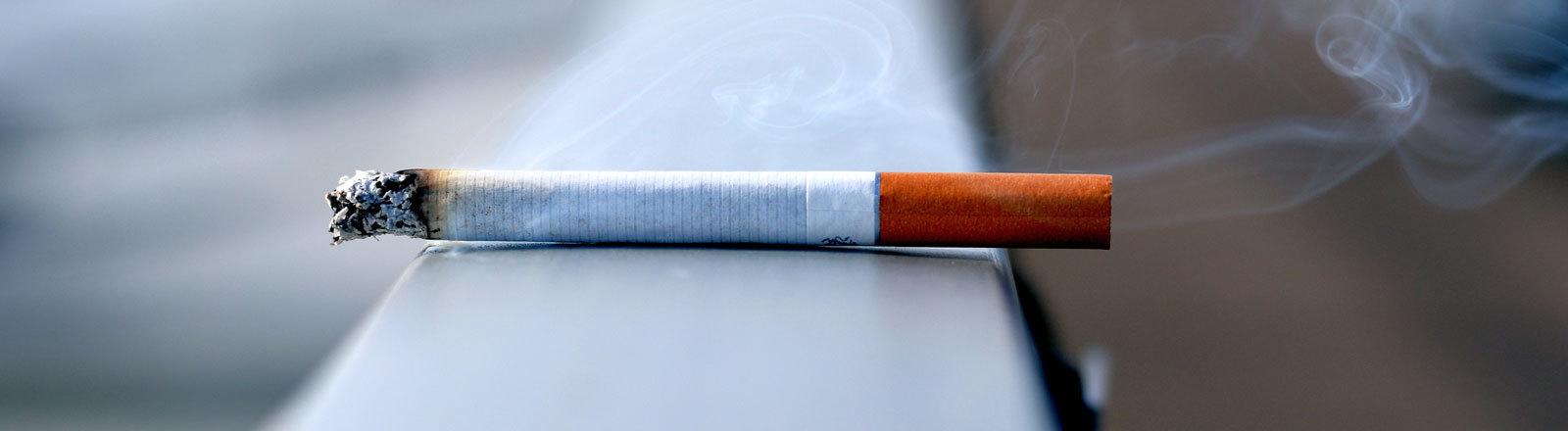Eine Zigarette liegt qualmend auf einem Geländer.
