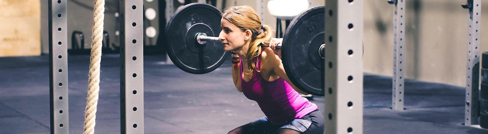 Eine Frau trainiert mit Gewichten in einem Fitnessstudio