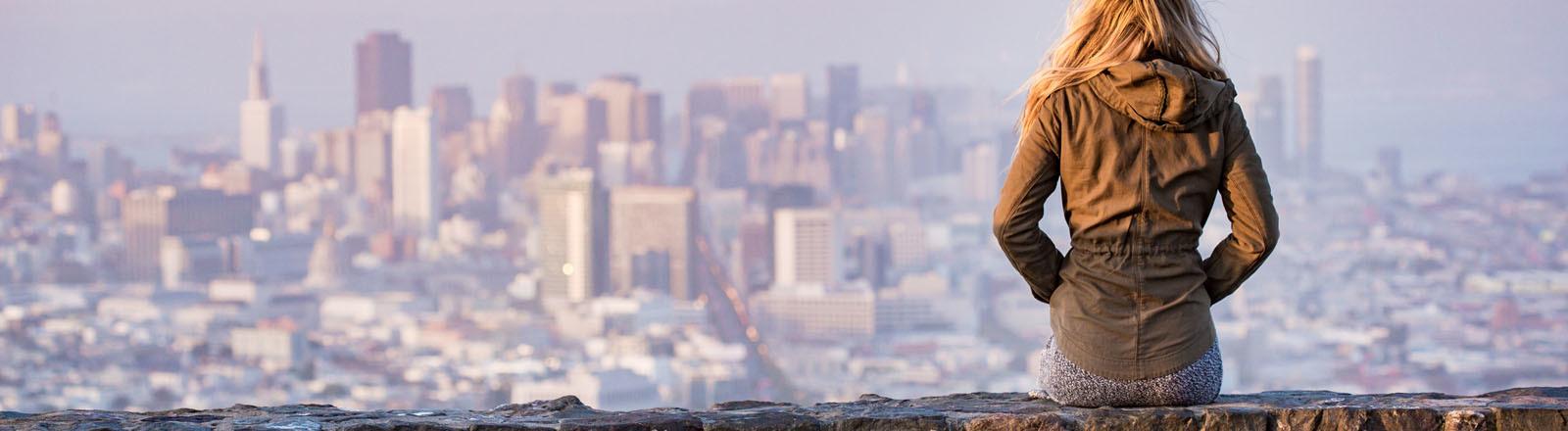 Eine Frau schaut von einer Mauer auf einem Berg auf eine Stadt herab.