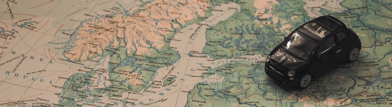 Europakarte auf der ein Spielauto steht.