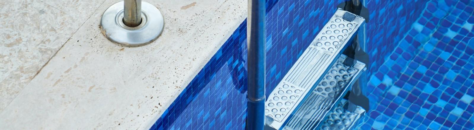 Eine Treppe führt in einen leeren Pool.
