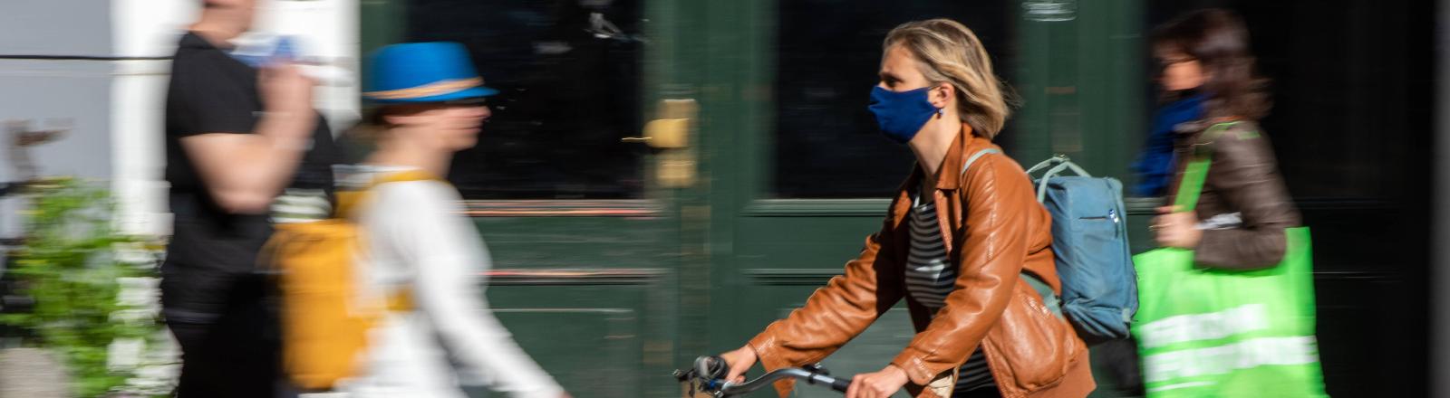 Frau auf Fahrrad mit Maske