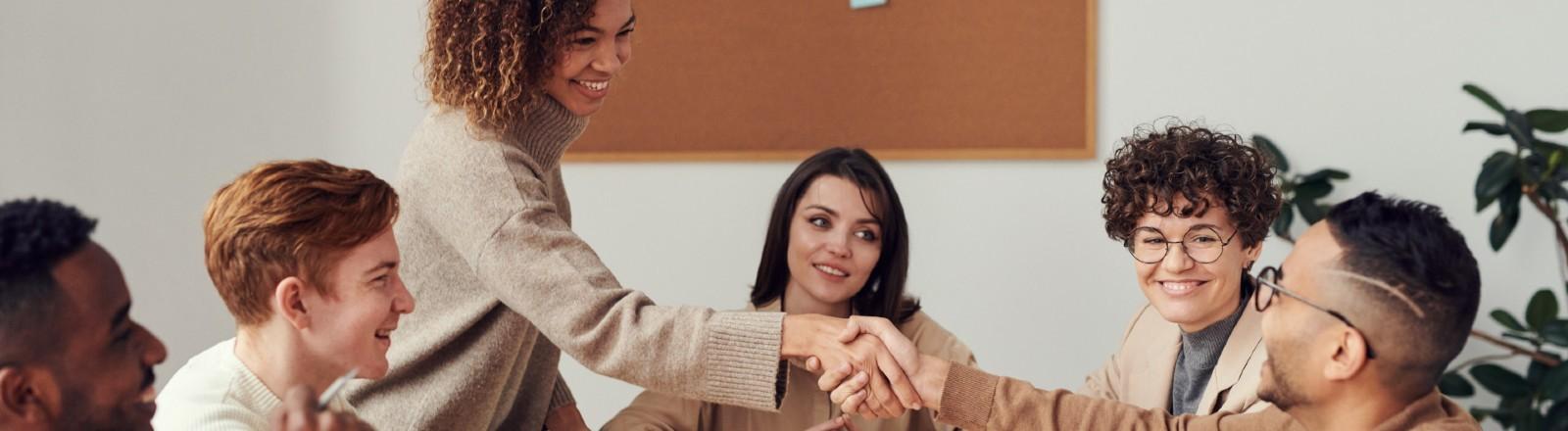 Mitarbeiter sitzen um den Konferenztisch, zwei geben sich die Hand. Freundliche Atmosphäre.