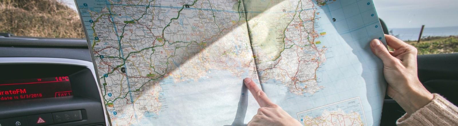 Eine Frau sitzt im Auto und zeigt mit dem Finger auf einer Landkarte, wo sie als nächstes hinreisen will.