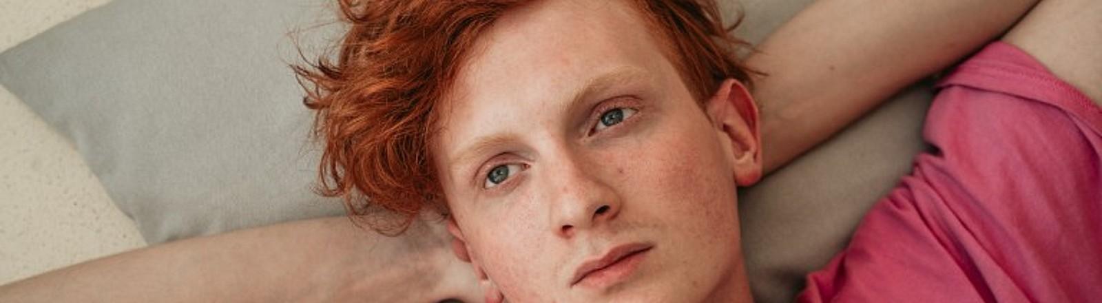 Junger Mann mit roten Haaren und pinkem Tshirt liegt auf dem Bett, schaut gedankenverloren nach oben an die Decke.