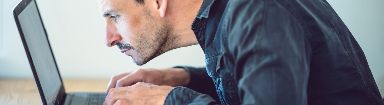 Ein Mann sitzt konzentriert am Laptop.
