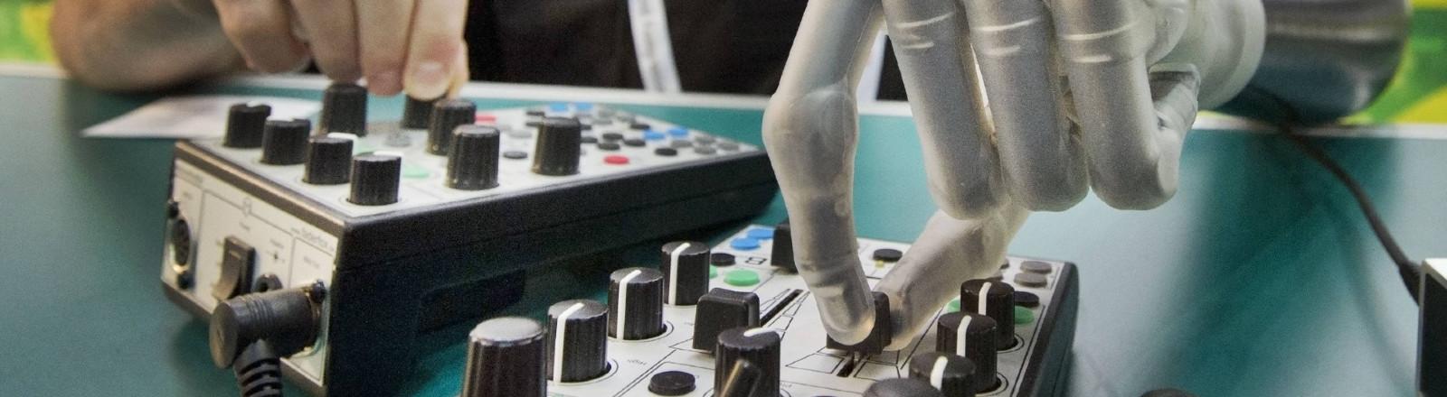 Mann mit Armprothese bedient Synthesizer.
