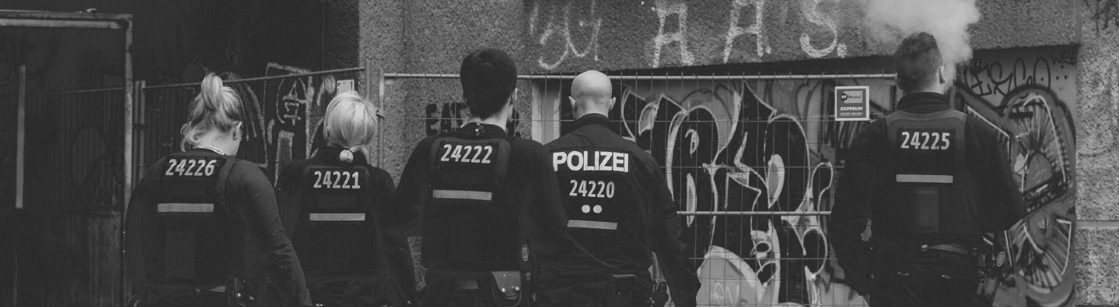 Fünf Polizisten sind von hinten zu sehen, wie sie auf einer Straße in Berlin laufen.