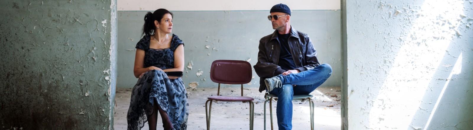Eine Frau und ein Mann sitzen in einer leeren Halle auf Stühlen und blicken sich vorwurfsvoll an.