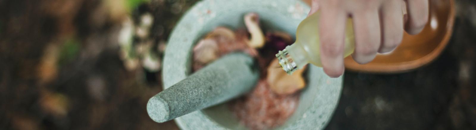 Hand gießt Flüssigkeit in eine Schale mit Mörser.