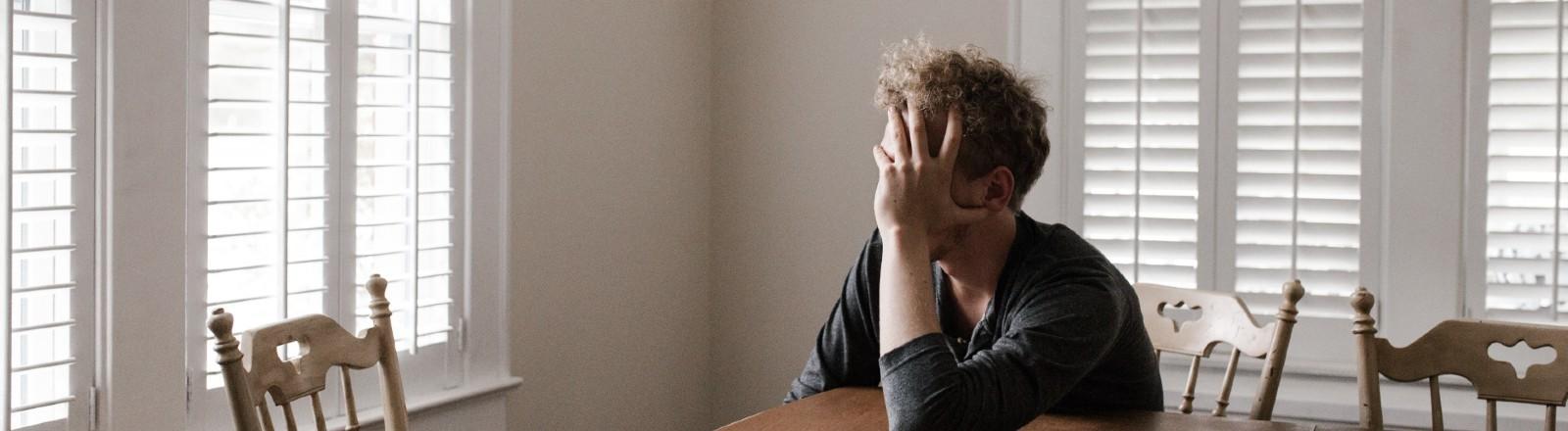Ein Mann sitzt am Tisch, die Sonne scheint rein und er legt müde sein Gesicht in die Hand.