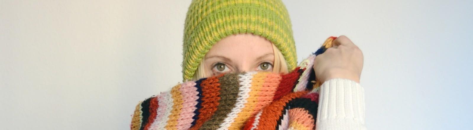 Eine Frau trägt Mütze und einen Schal.