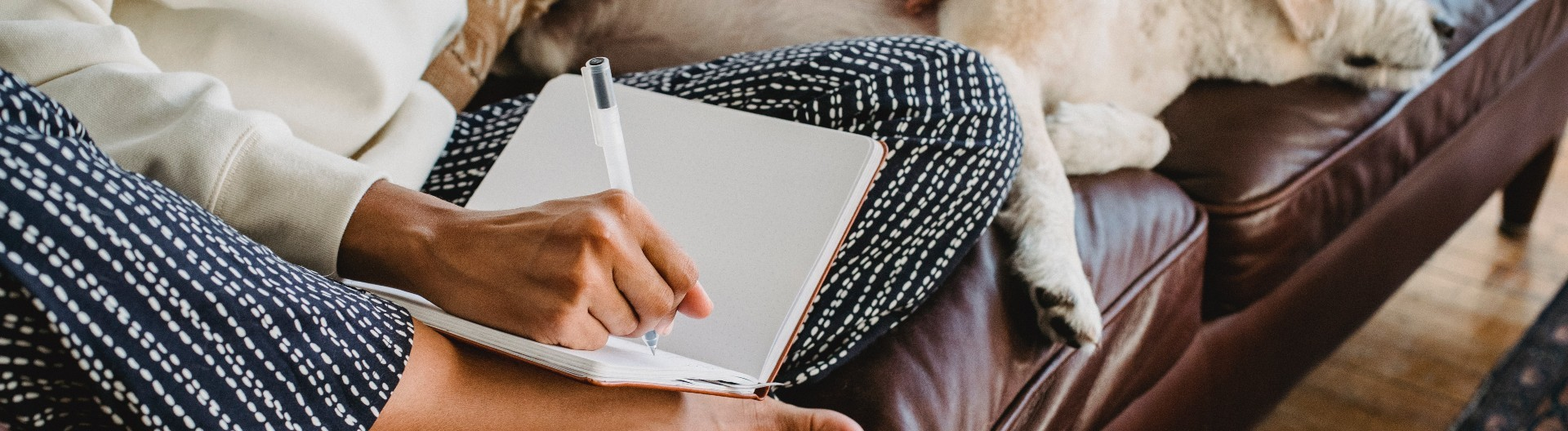 Eine Frau sitzt im Schneidersitz auf der Ledercouch und schreibt in ein Tagebuch.