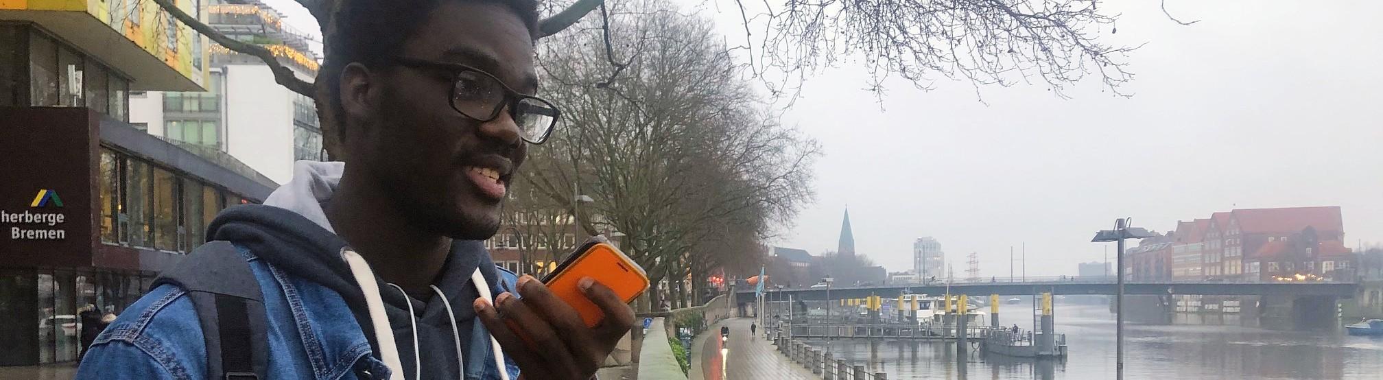 Bonaventure Doussau hält sein etwas ramponiertes Smartphone in der Hand.