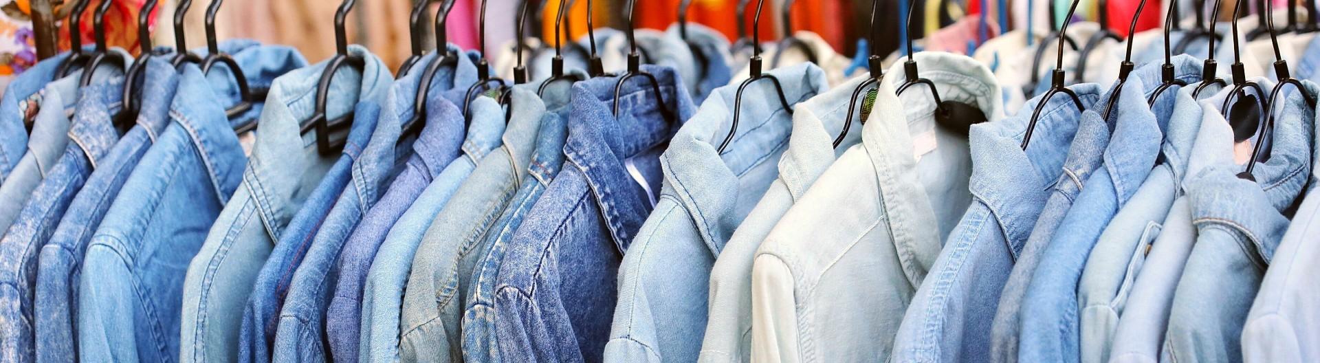 Viele Jeanshemden hängen hintereinander an einer Stange.