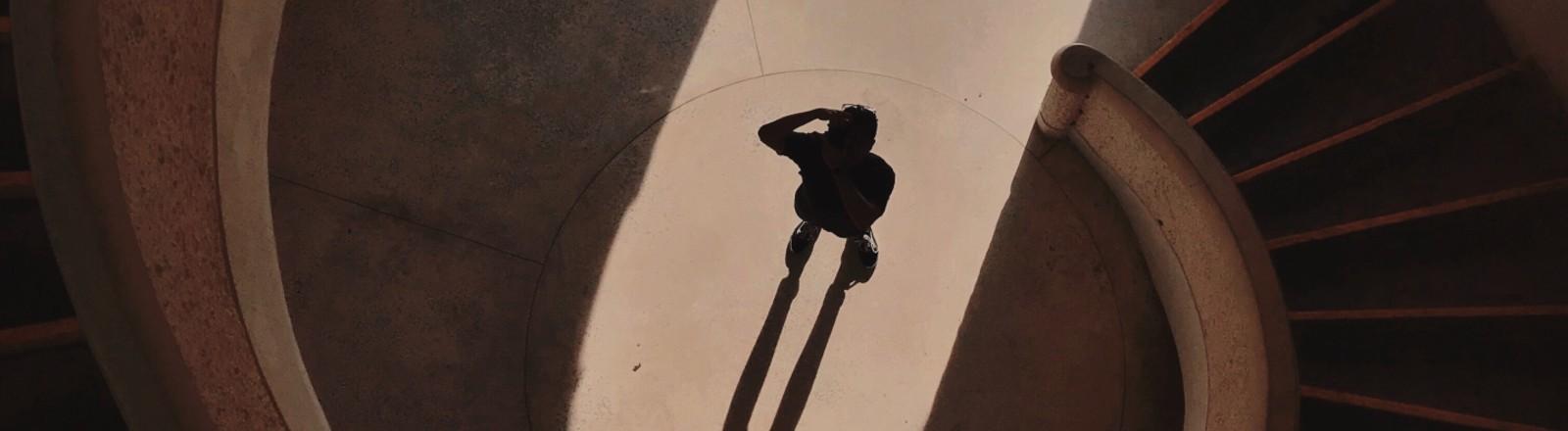 EIne runde Treppe, Schatten, Licht von draußen, ein Mensch steht in der Mitte.