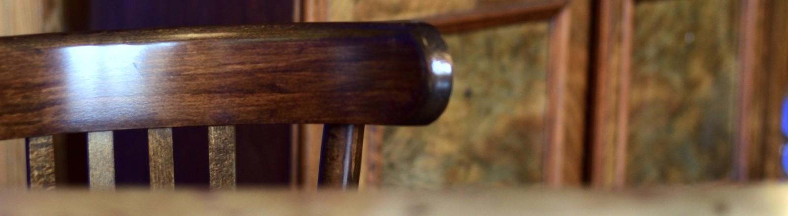 Ein leerer Holzstuhl an einem Tisch.