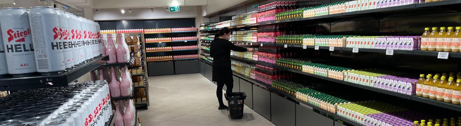 Eine Frau steht in einem sehr aufgeräumten Supermarkt am Regal.
