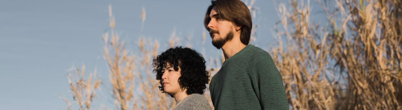 Freunde, Mann und Frau, stehen in den Dünen und schauen nachdenklich in die Ferne.
