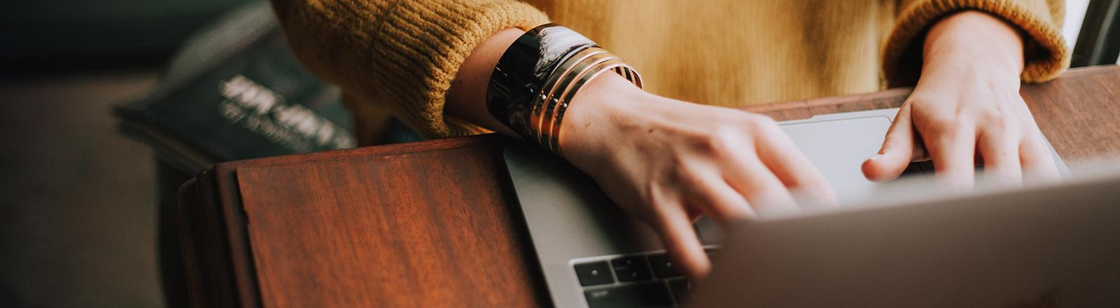 Frauenhände tippen auf einer Laptop-Tastatur