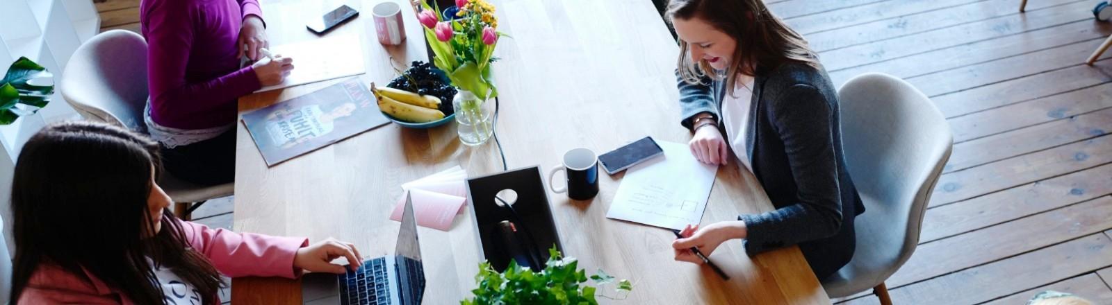 Frauen sitzen an einem Tisch und arbeiten zusammen