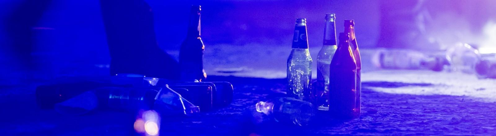Flaschen liegen im Volkspark Hasenheide auf dem Boden, nachdem die Polizei eine Menschenansammlung aufgelöst hat.