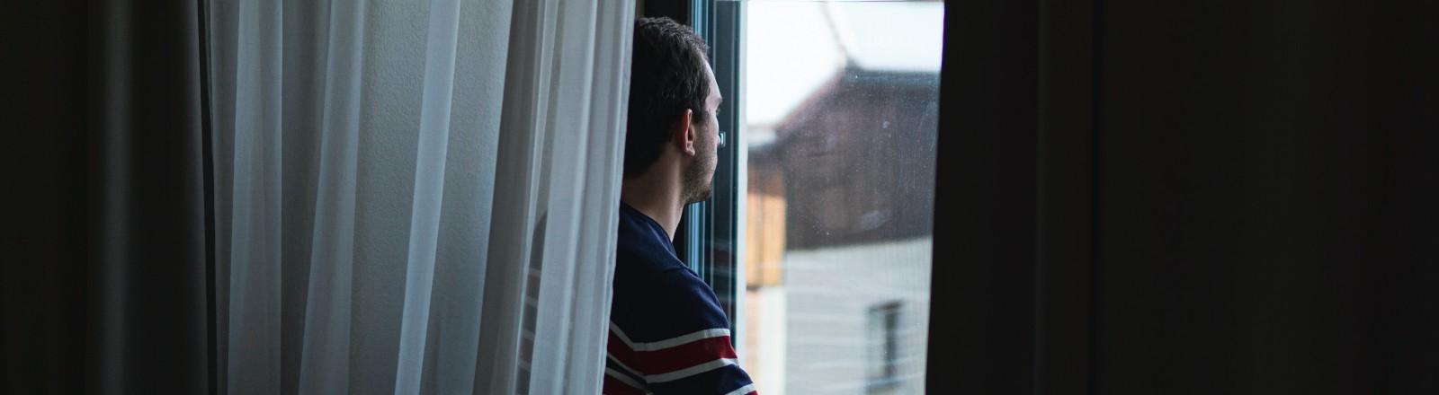 Ein Mann sitzt auf einer Fensterbank und schaut nach draußen auf ein Haus.