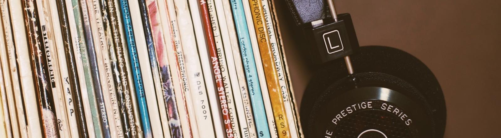 Schallplatten stehen in einem Regal. Daneben liegen Kopfhörer.