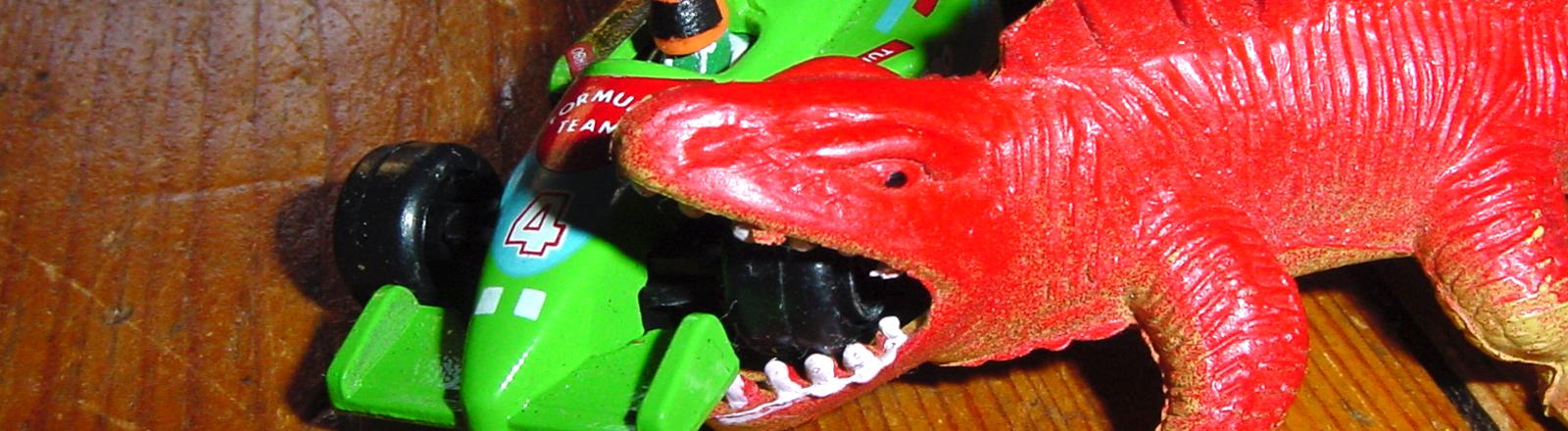 Spielzeugdino beißt in Spielzeugrennauto.