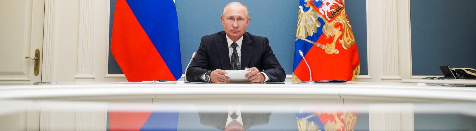 Wladimir Putin sitzt an einem Konferenztisch