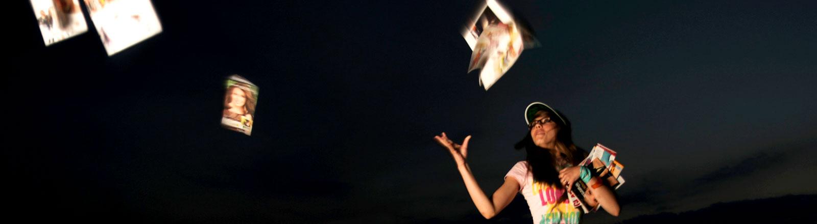 Eine junge Frau wirft Bücher in die Luft