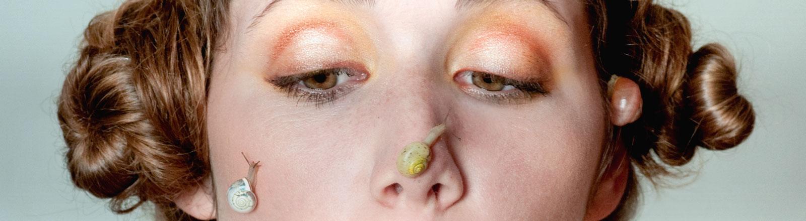 Eine Frau hat Schnecken auf ihrem Gesicht sitzen.