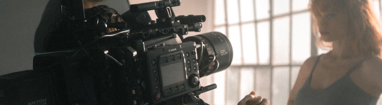 Eine Frau steht vor einer Filmkamera