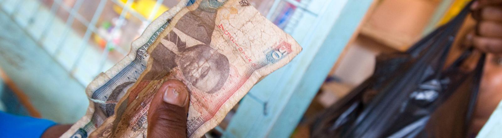 Eine Person zahlt mit kenianischen Schilling für Saatgut.