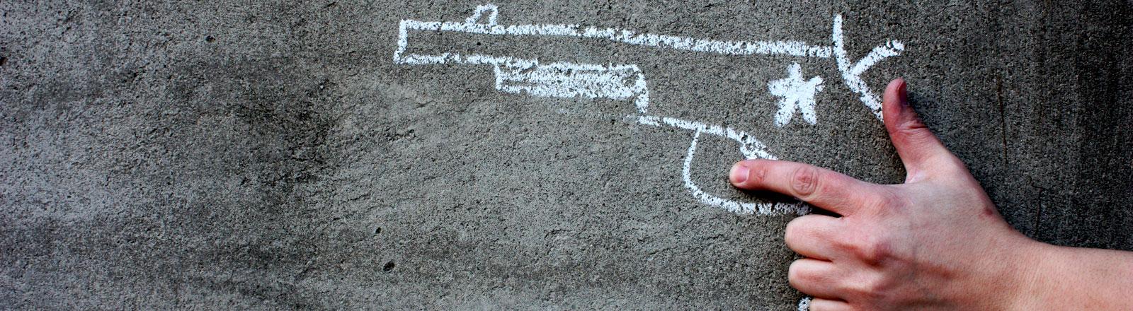 Eine Hand hält einen Colt, der mit Kreide auf eine Hauswand gemalt ist.