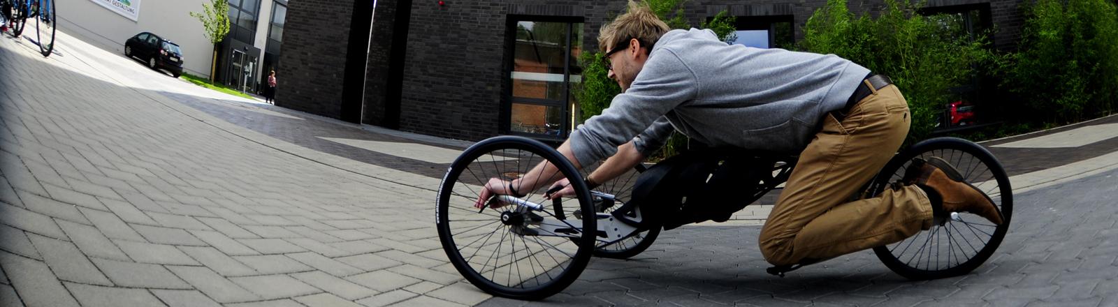 """Thyll Niebergall, Produktdesinger an der Hochschule für angewandte Wissenschaft und Kunst (HAWK) liegt in Hildesheim auf einer """"Menschmaschine"""", einem speziell entwickelten Fahrrad mit Akkuschrauber-Antrieb."""