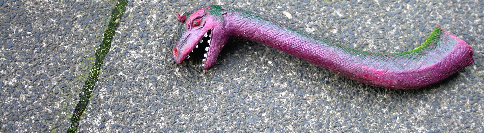 Kopf mit Hals von Spielzeugdino auf dem Asphalt.