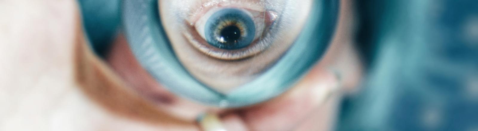 Blaues Auge durch eine Glaskugel.