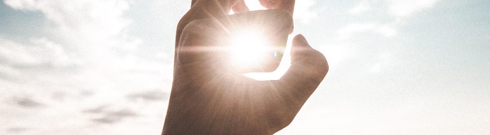Zwischen den Fingern einer Hand sieht man die Sonne.