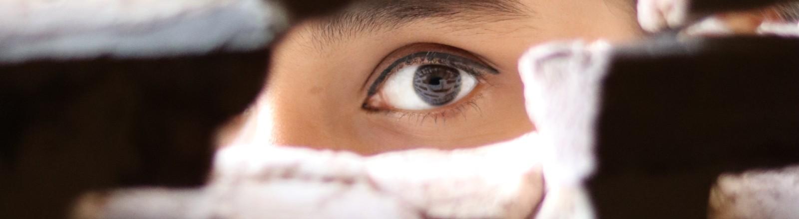 Eine Frau späht durch ein Loch in einer Wand und man sieht nur ihr Auge.