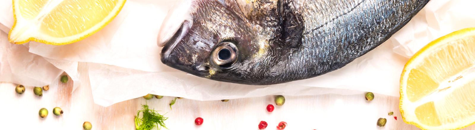 Fisch zubereiten mit Pfeffer, Salz und Zitrone.
