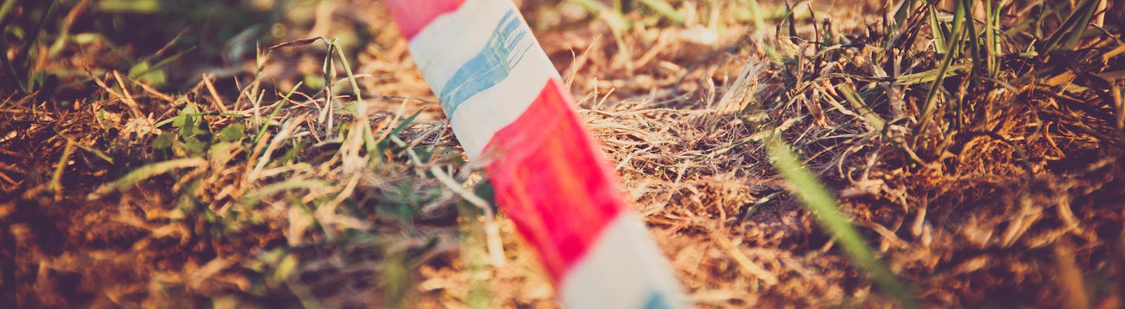 Absperrband auf dem Waldboden.